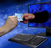 hand offering credit card through monitor